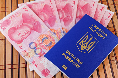 Ukrainian passport and yuans closeup on background of bamboo mat Stock Photo - 119149047