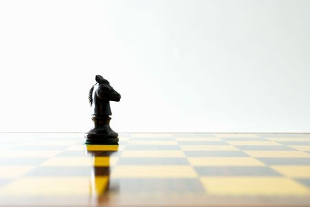 Knight and its reflection on a chess board photo