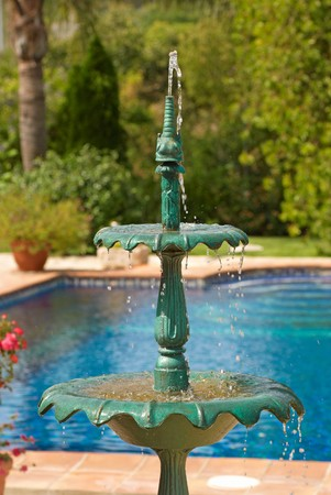 Classic small fountain splashing in a garden with large pool photo