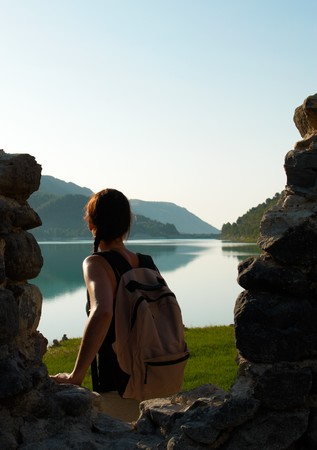 introspective: A young hiker in contemplative attitude enjoying an early morning landscape
