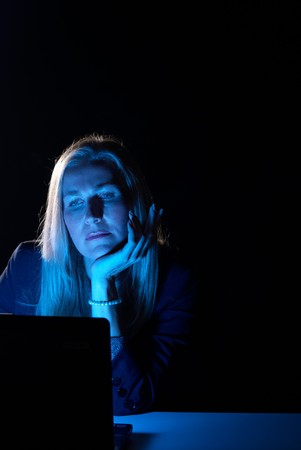 Blue computer screen reflecting on late working businesswoman Stock Photo - 7590844