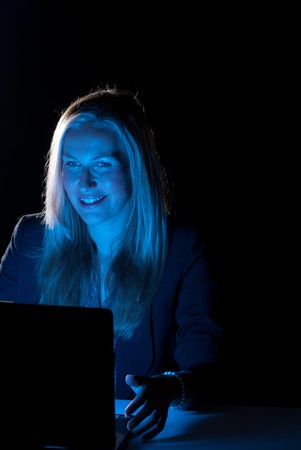 Businesswoman working late hours, with positive, smiling attitude photo
