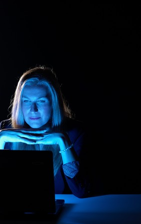 Businesswoman working late hours, concentrated on the laptop screen photo