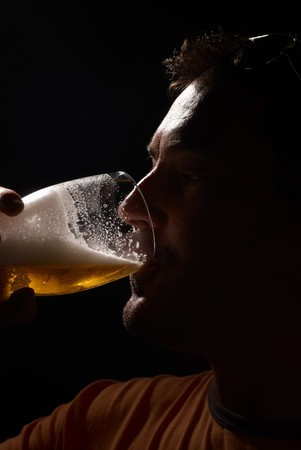 Silhouette portrait of a man enjoying a pint of beer Imagens