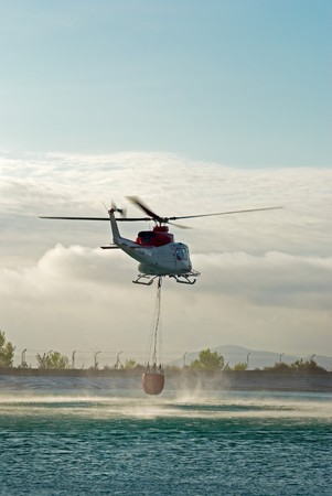 Fire brigade helicopter hovering over water while refilling the tank photo