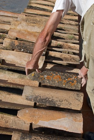 Construction worker interlocking spanish roof tiles photo