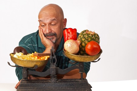 what to eat: Dieting man anxiously looking at what he should not eat