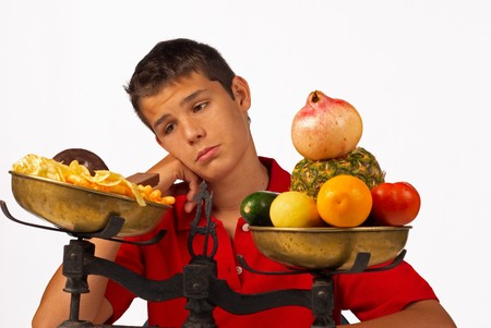 balanza en equilibrio: Adolescente mal querer comida basura uno en su lugar saludable  Foto de archivo