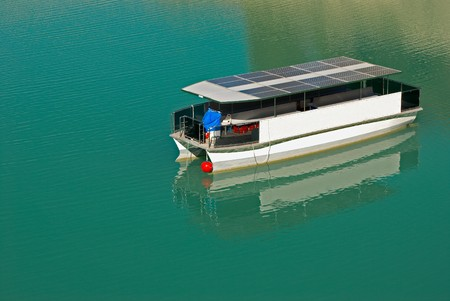New technology solar boat in calm lake waters Imagens