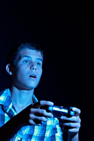 deranged: Teen with deranged facial expression while passionately gaming Stock Photo