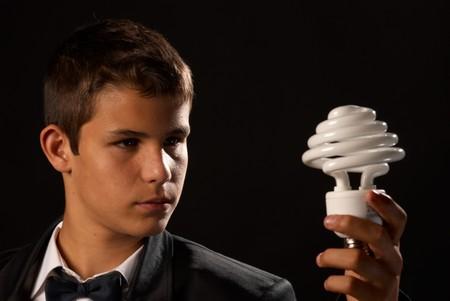 Environmental awareness, teen holding a energy saving bulb photo