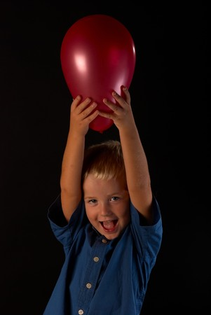 Blond boy cheering with his red balloon Stock Photo - 7841103