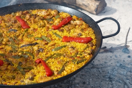 Traditional outdoor cooking of paella on open fire