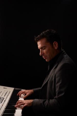 instrumentalist: Elegantly dressed up musician playing a keyboard