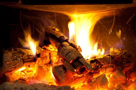 Burning logs in a cosy living room chimeney photo