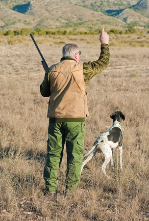 out of order: Quail hunter in camouflage clothing walking across the field Stock Photo