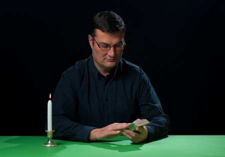fourties: Tarot reader in full concentration about to start spreading the cards Stock Photo