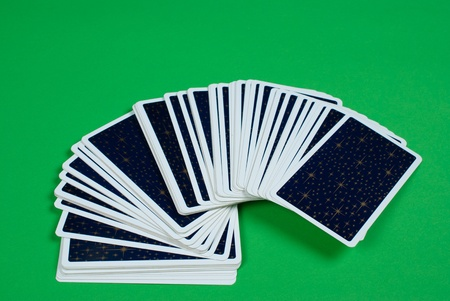 fanned: Deck of tarot cards fanned out on a green table