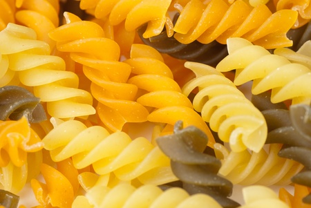 A heap of multicolored raw rotini, food background photo