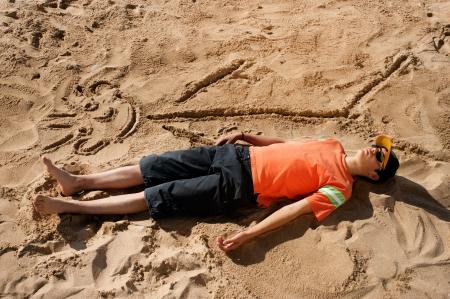 Artistic teenager sunbathing next to his beach cartoon Stock Photo - 8937340