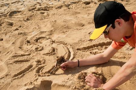 Creative teenager sketching a cartoon on beach sand Stock Photo - 8937374