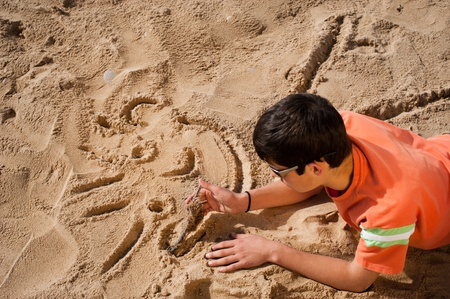 Creative teenager sketching a cartoon on beach sand Stock Photo - 8937373