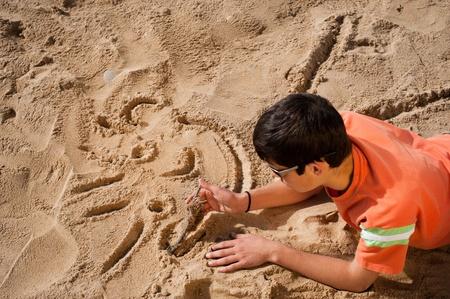 Creative teenager sketching a cartoon on beach sand Stock Photo - 8937373