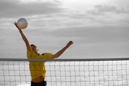 Teenager in action during a match of beach volley photo