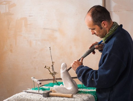 Scultore lavorando sulla sua arte al suo workshop