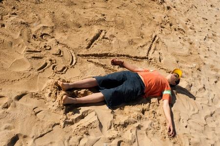 Creative teenager sunbathing next to his cartoon Stock Photo - 9001029