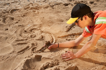 Creative teenager sketching a cartoon on beach sand Stock Photo - 9001039