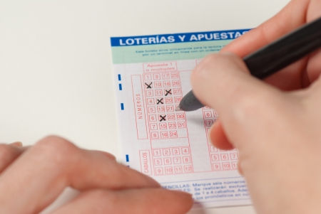 Female hands with pen filling in a lottery ticket Stock Photo - 9001031