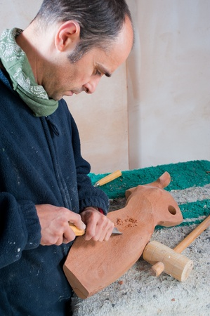 Artisan cocentrated working on  a wooden sculpture photo