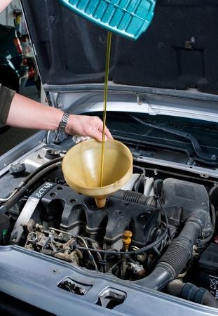 desague: Mec�nico de autom�vil llenado de aceite fresco en un motor Foto de archivo