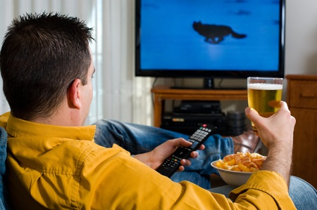 Guy enjoying his evening watching television from the sofa Stock Photo - 9133698