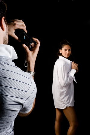 Guy taking photographs of his girlfriend in a studio environment Stock Photo - 9219691