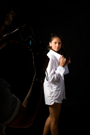 Guy taking photographs of his girlfriend in a studio environment Stock Photo - 9219715