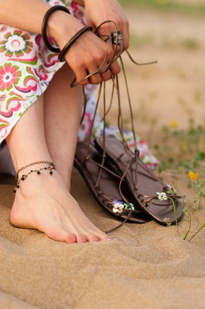 mujer hippie: Pies femeninos y sandalias de cuero sobre una duna de arena en primavera Foto de archivo