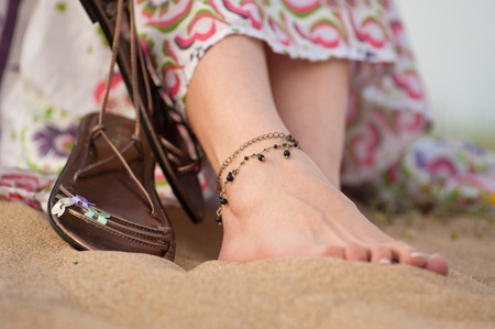 Female feet and leather sandals on a sandy dune in spring Stock Photo