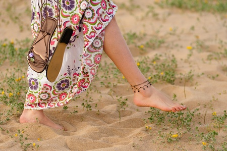 sandal: Girl walking barefoot on a dune with spring colours