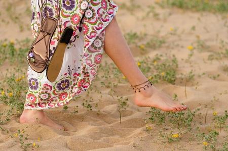 figli dei fiori: Ragazza che cammina a piedi scalzi su una duna con i colori della primavera