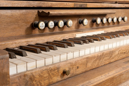 Vintage  wooden organ keyboard with its row of stops