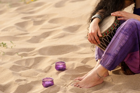 Hands of a woman holding a djembe on a sandy beach photo