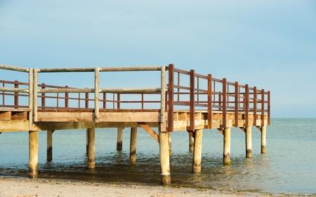 Wooden footbrige on an idyllic calm beach photo