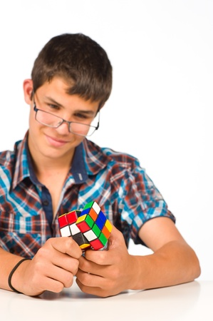 Nerdish teenager  concentrated playing with a cube Stock Photo - 9406221