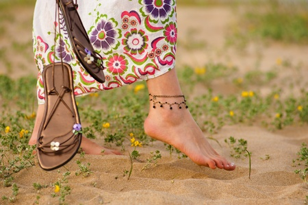 barefoot people: Girl walking barefoot on a dune with spring colours