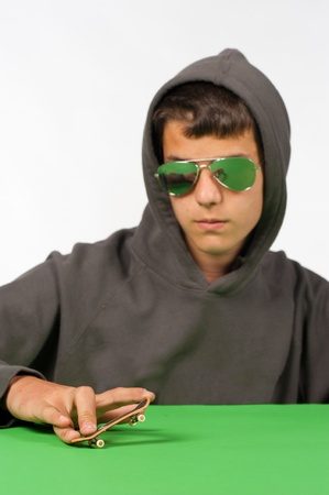 Cool teen posing with a tiny toy skateboard Stock Photo - 9422358