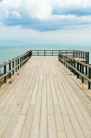 Traditional wooden footbridge  facing  a dramatic ocean setting photo