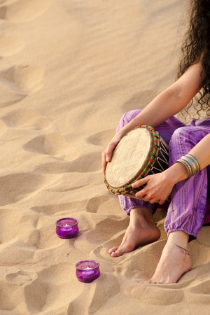 Hands of a woman playing a djembe on a sandy beach photo