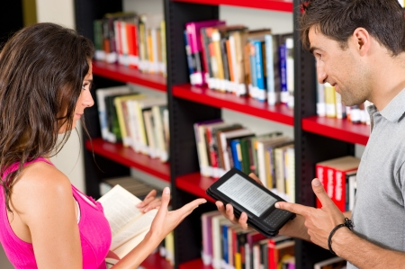 Couple choosing between paper and e-book Stock Photo